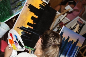 Photo of canvases filled with paintings of Chicago skyline at Chicago Smock painting party