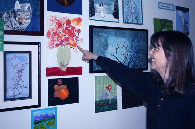 Photograph of Christy Alden Pointing to her student's art by Lynn S. Schwebach