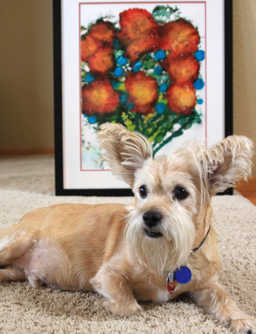 Photograph of an ink painting by Lynn S. Schwebach with her dog Kennedy sitting in front of it.